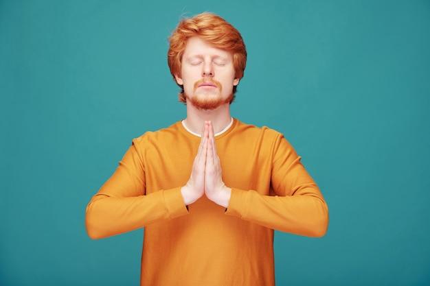 Rustige spirituele jonge roodharige man met baard die namaste-gebaar maakt tijdens het mediteren met gesloten ogen op blauw