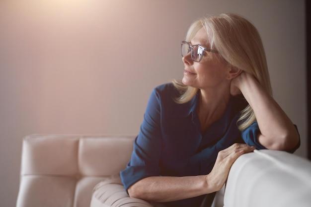 Rustige volwassen vrouw in brillen ontspannen op een bank thuis in de woonkamer