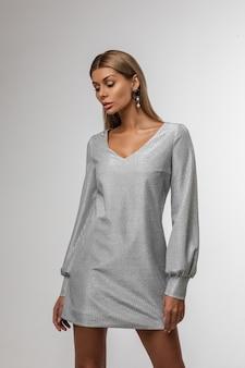 Rustige vrouw in een korte jurk en mooie oorbellen staan en naar beneden te kijken, op grijs