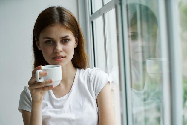 Rustige vrouw met een kopje in de buurt van het raam kijkt naar de camera