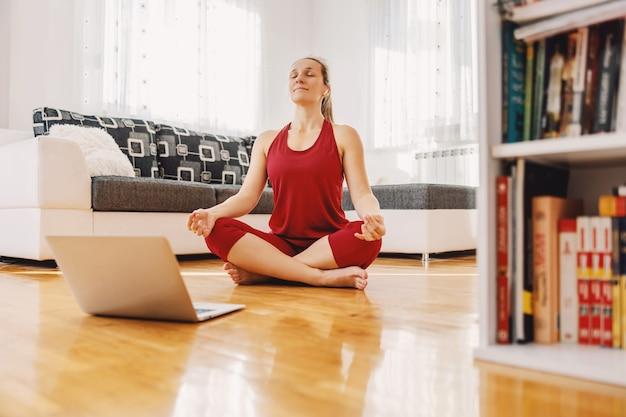 Rustige yoga-instructeur zittend in lotus yoga pose op de vloer thuis en met een online les.