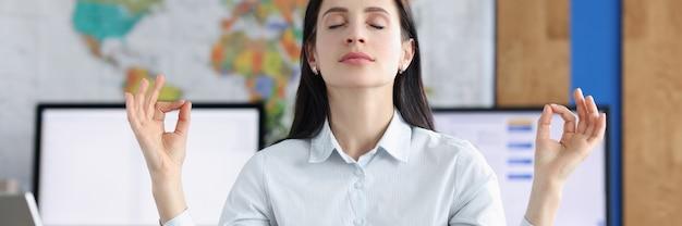 Rustige zakenvrouw die yoga-oefeningen doet op de werkplek