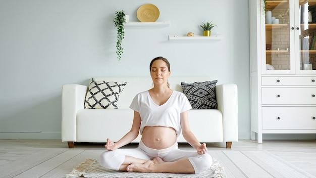 Rustige zwangere vrouw mediteert thuis in lotushouding