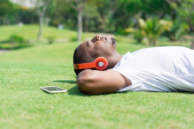 Rustige zwarte mens die in park rust en aan muziek luistert.