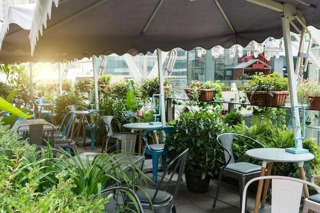 Rustruimte met tafels en houten stoelen onder paraplu in de tuin