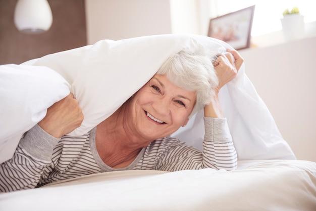 Rustte hogere vrouw in haar slaapkamer