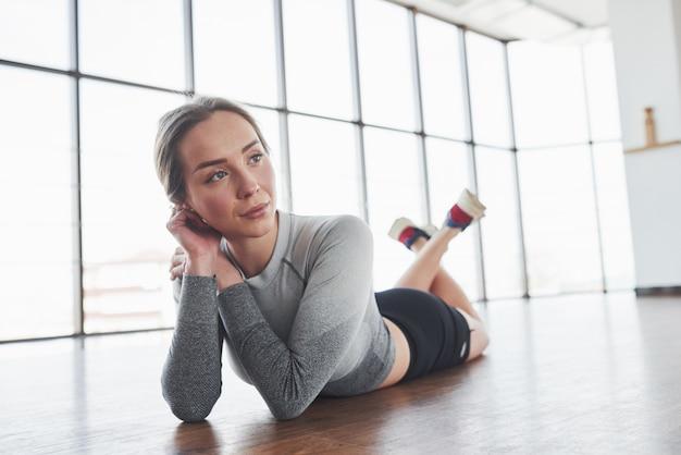 Rusttijd. sportieve jonge vrouw heeft fitnessdag in de sportschool in de ochtendtijd