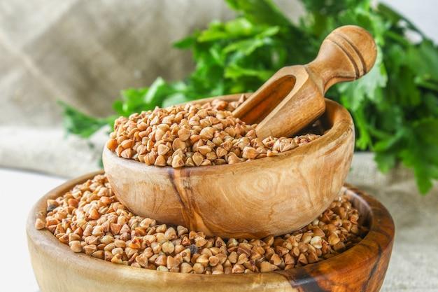 Ruw boekweit in houten kommen en een lepel op jute op een houten achtergrond. gezonde voeding voedsel
