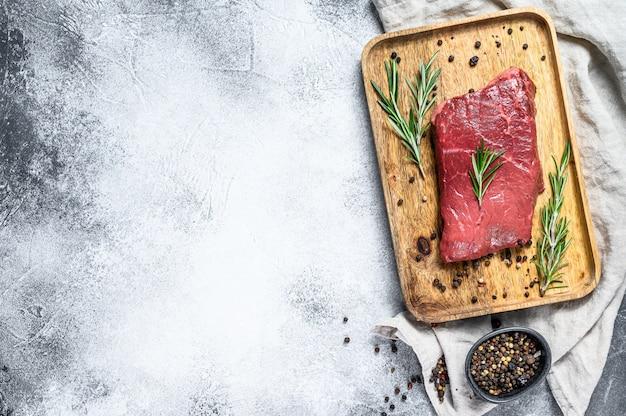 Ruw de strooklapje vlees van new york op een houten dienblad. rund vlees. bovenaanzicht copyspace-achtergrond