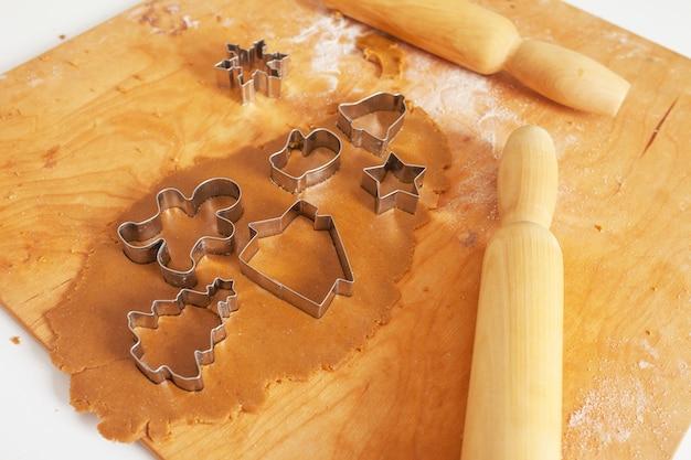 Ruw deeg, deegrollen en koekjesmessen voor kerstkoekjes op een houten bord. voorbereiding op de vakantie, kerstmis, nieuwjaar.