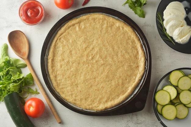 Ruw deeg en verse ingrediënten voor pizza. kopieer ruimte.