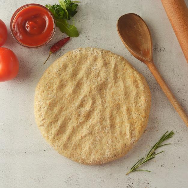 Ruw deeg voor pizza met ketchup. kopieer ruimte.