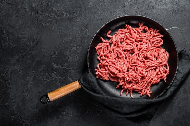 Ruw fijngehakt varkensvlees in een pan. bovenaanzicht