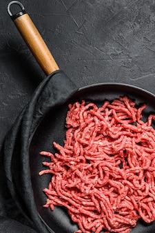 Ruw fijngehakt varkensvlees in een pan. zwarte achtergrond. bovenaanzicht ruimte voor tekst
