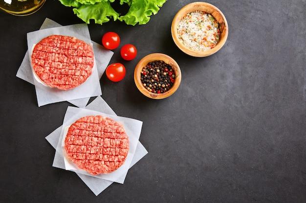 Ruw gehakt voor huisgemaakte grillburgers die met ruimten en kruiden koken.
