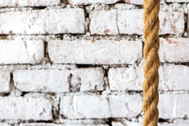 Ruw gevlochten touw tegen de achtergrond van een witte bakstenen muur in een luxe loft interieur van een hotelkamer.