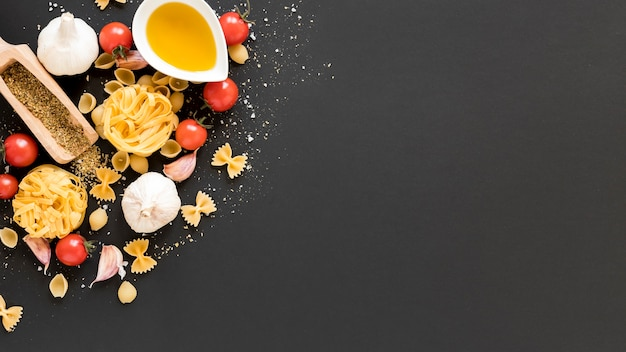 Ruw ingrediënt met tagliatelle; conchiclioni; tagliatelle; farfalle; olie op zwarte achtergrond