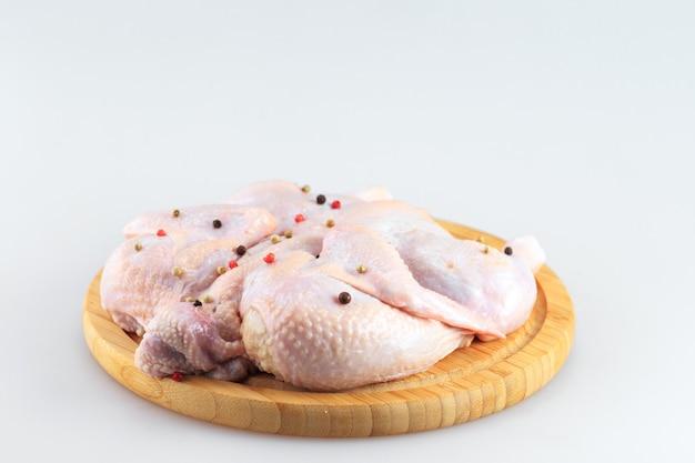 Ruw kippenkarkas op de scherpe die raad op witte achtergrond wordt geïsoleerd
