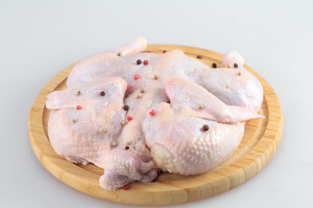 Ruw kippenkarkas op de scherpe raad die op wit wordt geïsoleerd