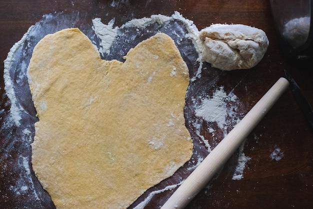Ruw ongezuurd deeg op keukenlijst, schommelbroodje, selectieve nadruk