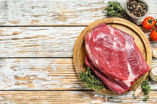 Ruw rond rundvlees dat op een houten raad wordt gesneden. witte achtergrond. bovenaanzicht. kopieer ruimte.