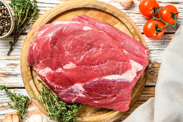 Ruw rond rundvlees dat op een houten raad wordt gesneden. witte achtergrond. bovenaanzicht.