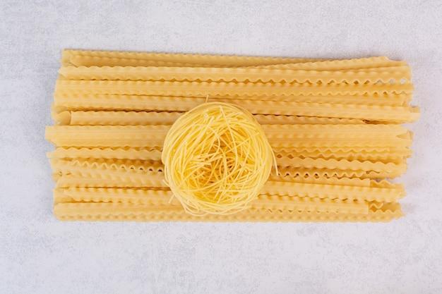 Ruw spaghettinest en lange deegwaren op steenoppervlakte