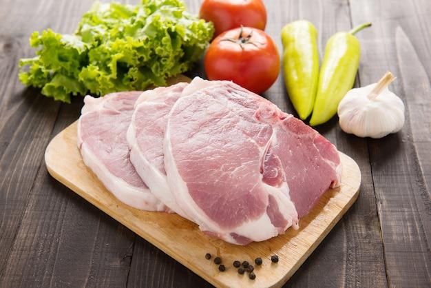 Ruw varkensvlees op scherpe raad en groenten op houten achtergrond