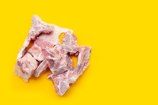 Ruw varkensvleesbeen op gele achtergrond.