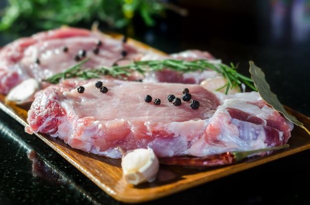 Ruw varkensvleeslapje vlees klaar voor het koken met spaanse pepers en rozemarijn