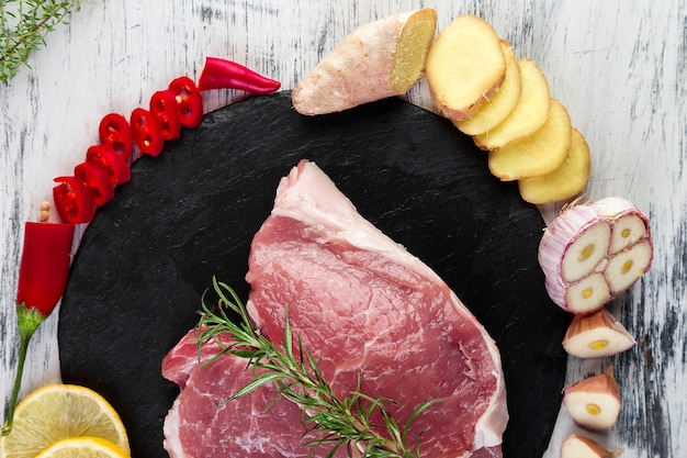 Ruw varkensvleesvlees op zwarte leiplaat met kruidingrediënt - rozemarijn, gember, spaanse peperspeper, ui. hoogste mening. plat leggen. kopieer ruimte.