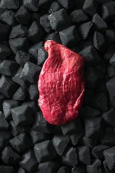 Ruw vers rundvleesvlees over een houtskool hoogste mening