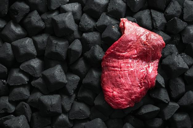 Ruw vers rundvleesvlees over een houtskool met exemplaar ruimte hoogste mening