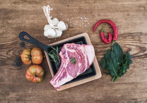 Ruw vers vleesribeye lapje vlees met peper, zout, spaanse peper, knoflook, spinazie, erfgoedtomaten en rozemarijn in het koken van pan over rustieke houten oppervlakte, hoogste mening.