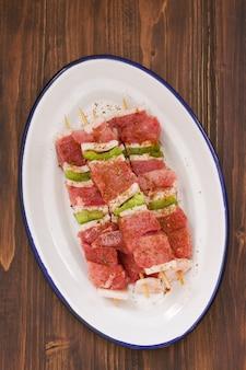 Ruw vlees met peper voor grill op witte schotel op houten lijst