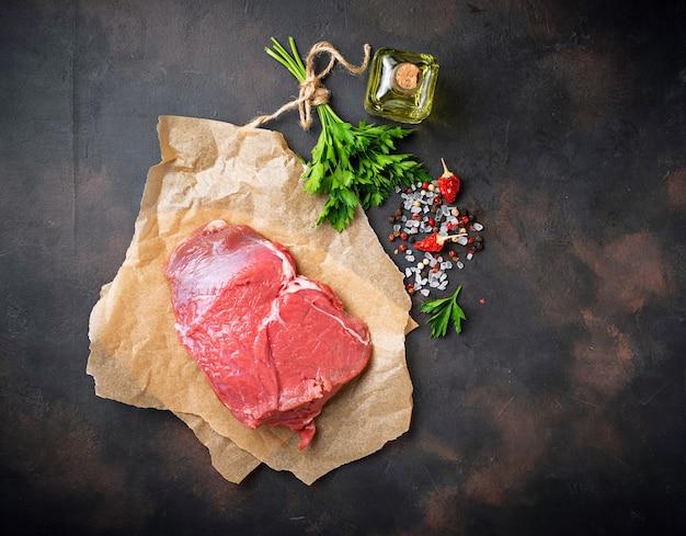 Ruw vleeslapje vlees met kruiden op roestige achtergrond