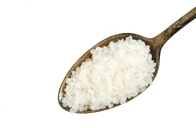 Ruw zout in een lepel op een witte achtergrond.