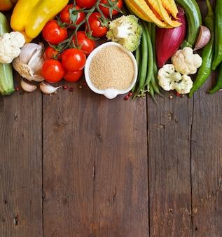Ruwe amarantkorrel in een kom en groenten op hout
