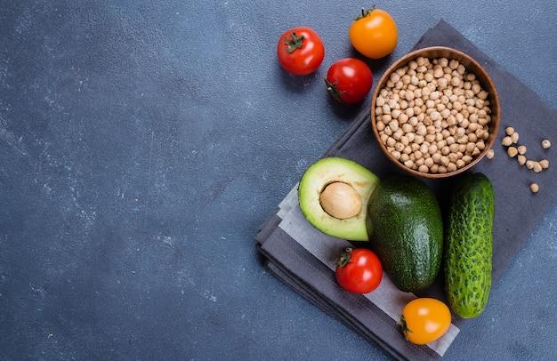 Ruwe avocado, komkommer, tomaat en kikkererwten op concrete stenen tafel achtergrond.