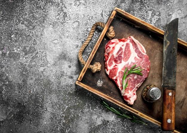Ruwe biefstuk op een oud dienblad. op rustieke achtergrond.