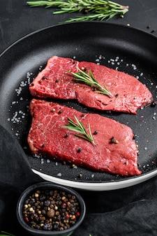 Ruwe biefstuk van het strooklendestuk in een pan. rund vlees. bovenaanzicht