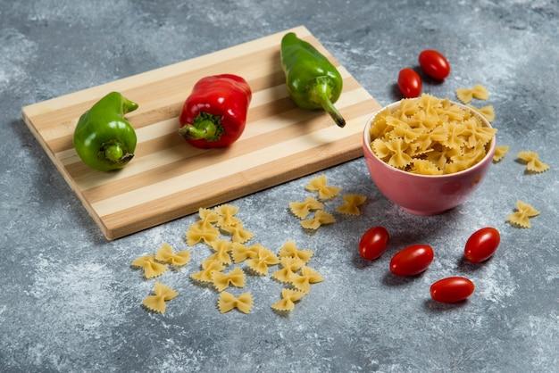 Ruwe bogen pasta met groenten op een houten bord.