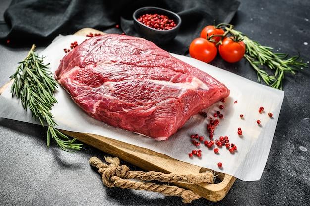Ruwe borst rundvlees gesneden op een houten snijplank. black angus-rundvlees. zwarte achtergrond. bovenaanzicht.