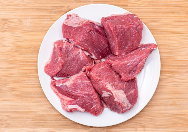 Ruwe brokken rundvlees voor bbq of goelasjvlees op witte plaat, hoogste mening