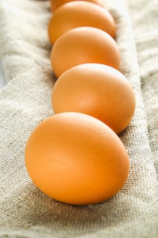 Ruwe bruine kippeneieren in één rij op jute op een witte houten lijst. ingrediënten voor het koken.