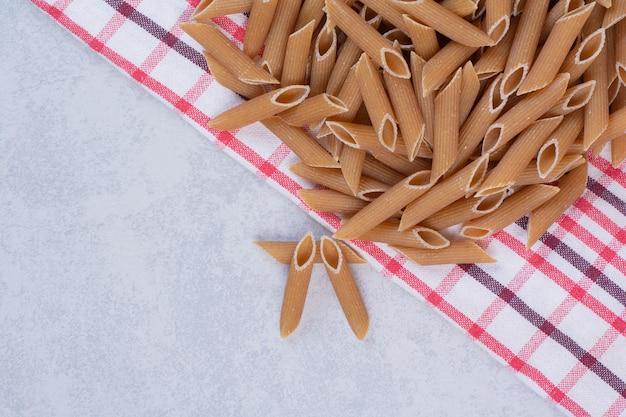 Ruwe bruine pennedeegwaren op gestreept tafelkleed