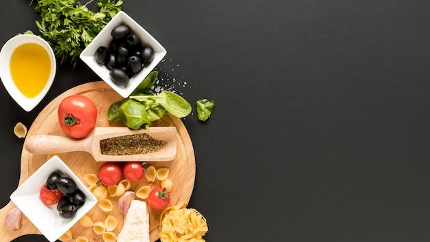Ruwe conchigliedeegwaren met ingrediënt over zwarte achtergrond