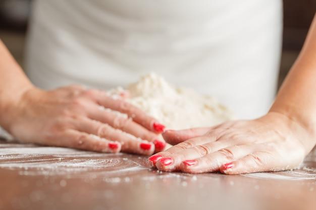 Ruwe deeg maken door vrouwelijke handen op tafel