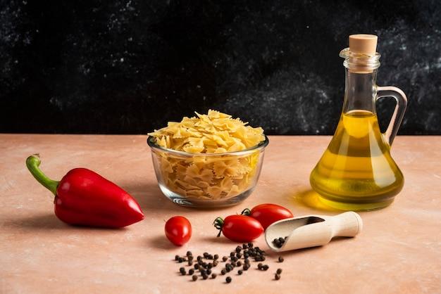 Ruwe deegwaren, groenten en fles olie op oranje lijst.