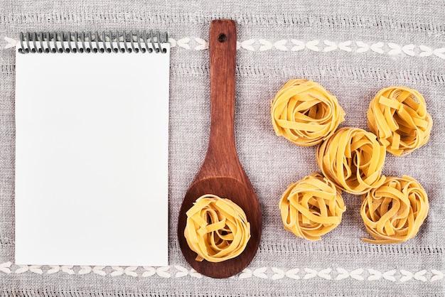 Ruwe deegwaren in een houten lepel met een receptenboek.